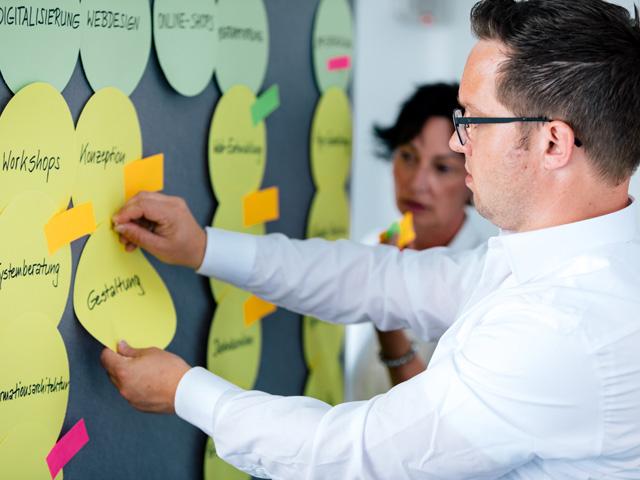 Mitarbeiter hängen Schlagwörter der Webentwicklung an Pinnwand an